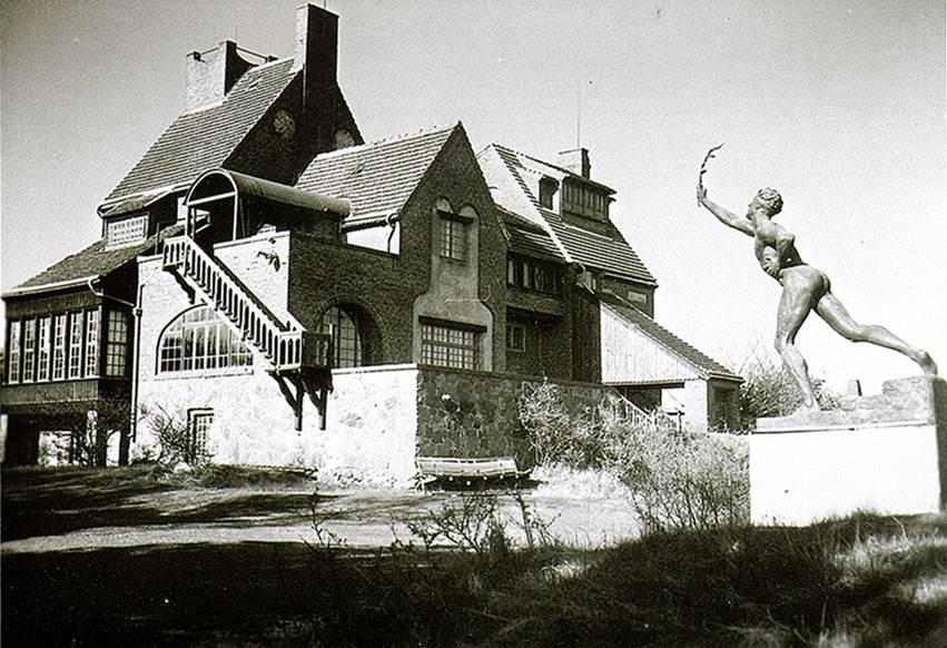 """Die Lietzenburg, im Vordergrund """"Der Siegesbote von Marathon"""" (undatiert, wohl 1920er Jahre; Bronzeskulptur von Max Kruse)"""